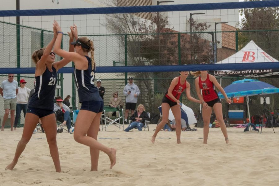 Warriors women's beach volleyball players Jordyn Bonitz and Jocelyn Lacroix high-five while Sierra Davis and Brooklin Mize of Long Beach City College talk to each other Friday, April 19, at El Camino's sand courts. Bonitz and Lacroix won the match with scores of 23-21, 16-21 and 15-9. Photo credit: Elena Perez