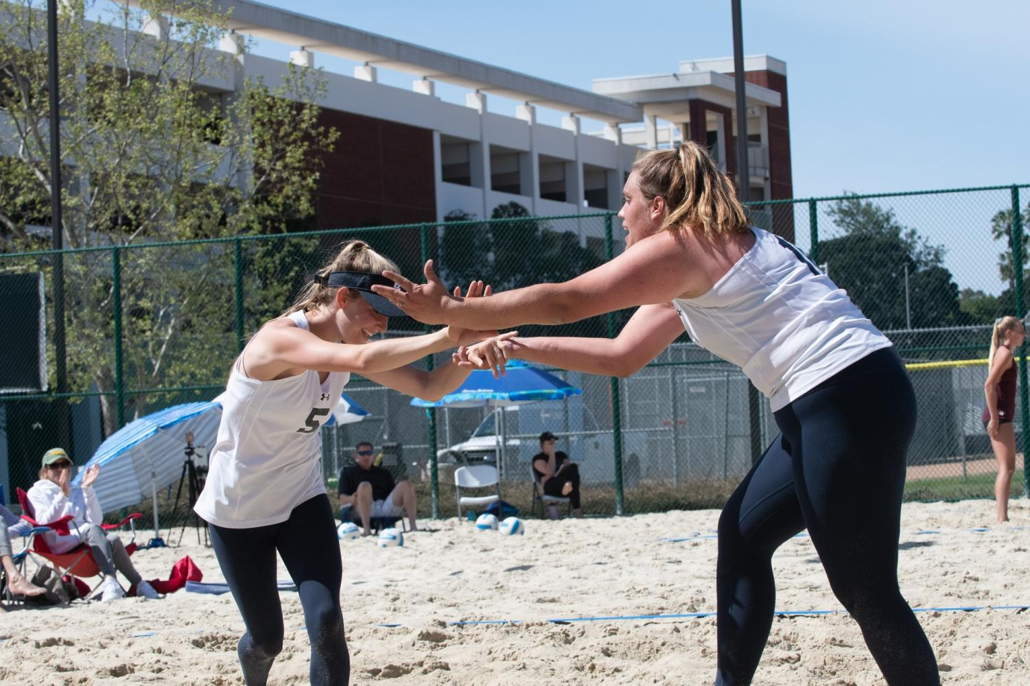 Warriors women's beach volleyball players Caitlin Donatucci (No. 5) and Sophia Loiola (No. 10) high-fiving each other in between sets during their doubleheader versus Mt. San Antonio and Santa Ana on Friday, March 29, at El Camino's sand courts. Photo credit: Elena Perez