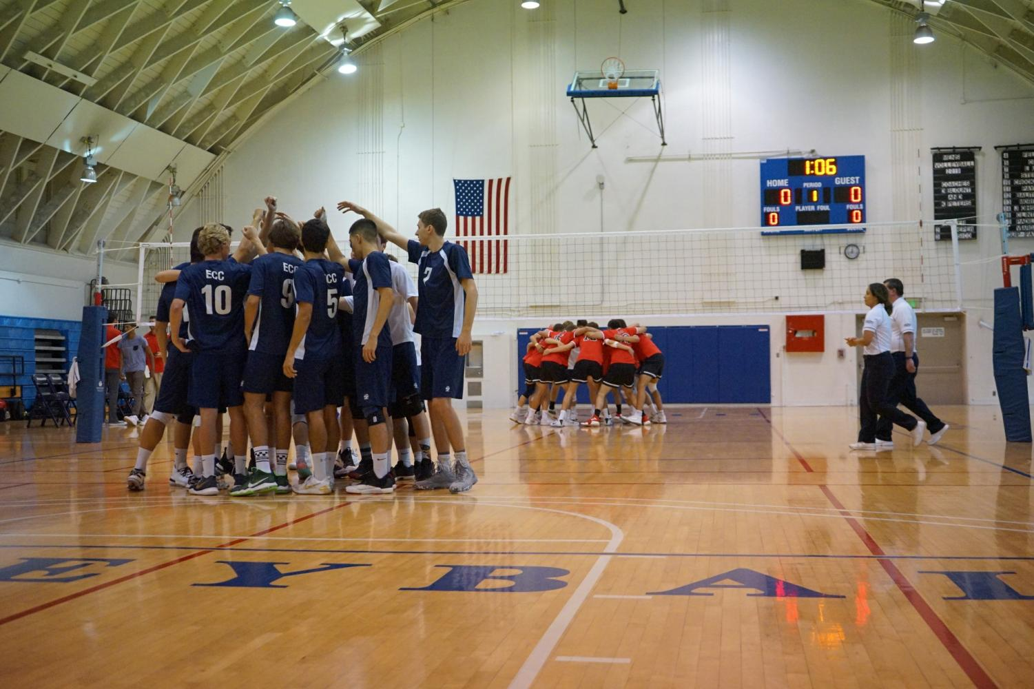 """Players from El Camino College and Santa Barbara City College huddling on their respective sides of the court before their match against each other on Wednesday, April 3. """"We came out kind of flat in the beginning, but as the game picked up, we were able to pick up the intensity and bounce back,"""" Warriors setter Joseph Sico said. Photo credit: Jun Ueda"""