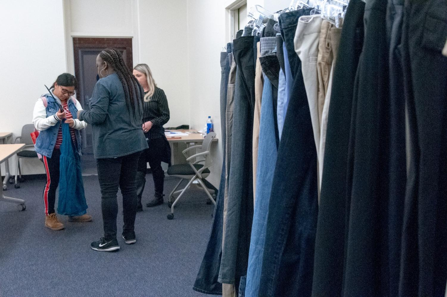 A student takes a dress off a hanger after she decides to take it with her on Wednesday, March 27. The goal of the Warrior Closet is to provide clothing to students in need. Photo credit: Elena Perez