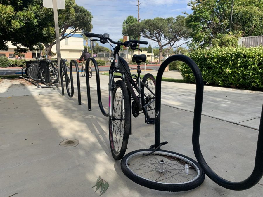 A bicycle wheel lays flat while still locked to an El Camino College bike rack near the Humanities Building on Wednesday, May 22. Bike thefts at EC have increased over the last two weeks. Photo credit: Fernando Haro