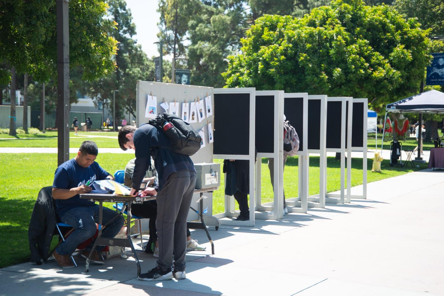 A student signs up to vote next to booths containing two voters on Wednesday, May 29. The results will be announced Friday, May 31. Photo credit: Jun Ueda