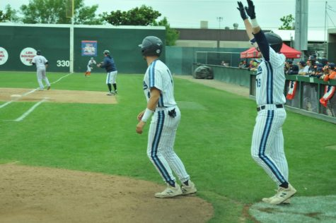 Warriors infielder Matt Beserra (left) and first basemen Spencer Palmer (right) watch a runner score versus the Orange Coast Pirates on Monday, May 27, at John Euless Ballpark in Fresno, CA. Beserra and Palmer combined for two hits, one RBI and one run. Photo credit: Devyn Smith