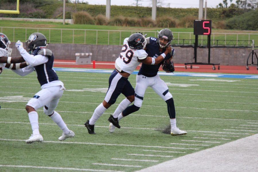 El Camino College football team wide receiver Isaiah Jones stiff arms an Orange Coast defender in the third quarter of the game against Orange Coast College on Saturday, Sept. 28 at Murdock Stadium. Jones finished he game with three receptions for 39 yards. Kealoha Noguchi/The Union