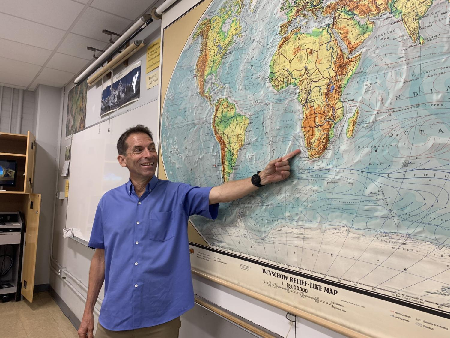 """ECC geography professor of 30 years, Matt Ebinor, points to where the Namibia and South Africa border is located during one of his geography lectures on Tuesday, Sept. 3. When Ebiner is not teaching at ECC he organizes tours to different countries. """"It keeps me busy and is a kind of extension of my geography teaching,"""" Ebiner said. Photo credit: Anna Podshivalova"""