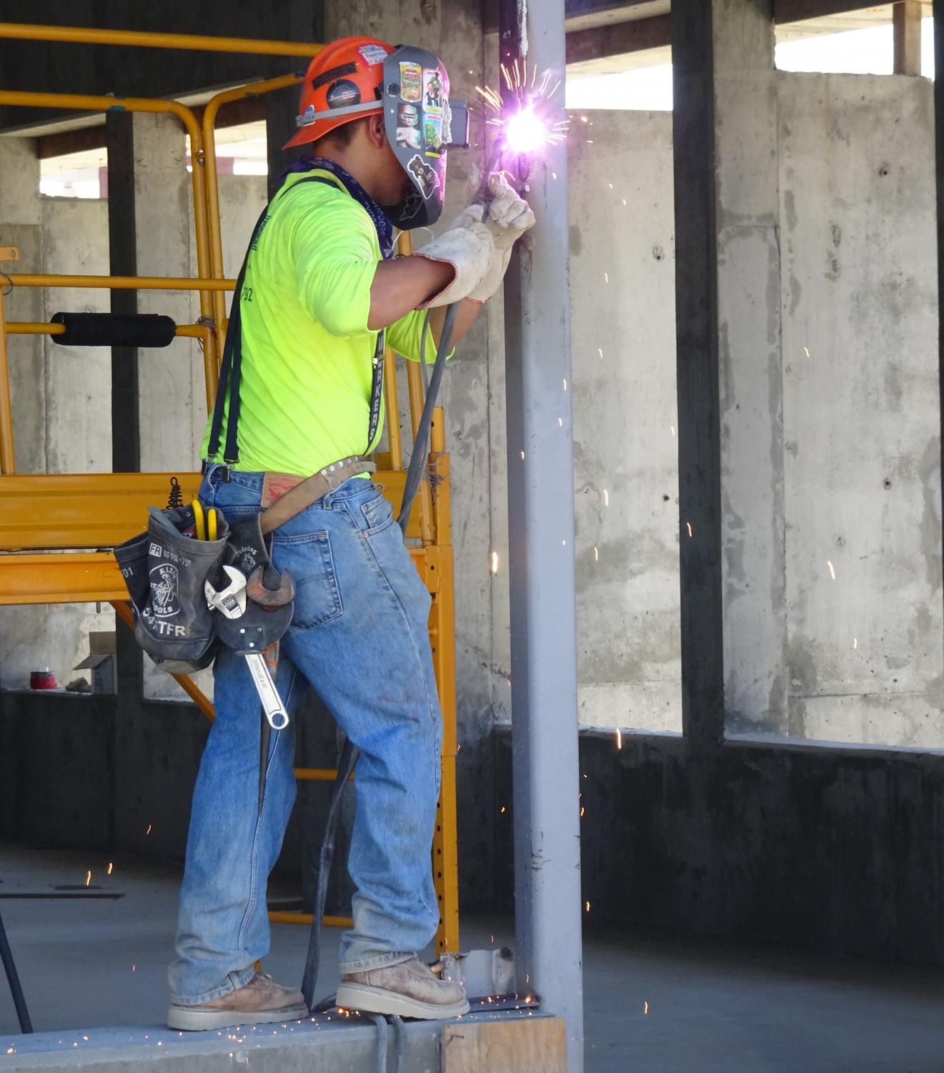 A construction worker welds a metal beam at the Pool and Classroom Building construction site Thursday, Aug. 29. Welding was the cause of a small fire on the building's second floor on the second day of the fall semester. Ryan Farrell/The Union