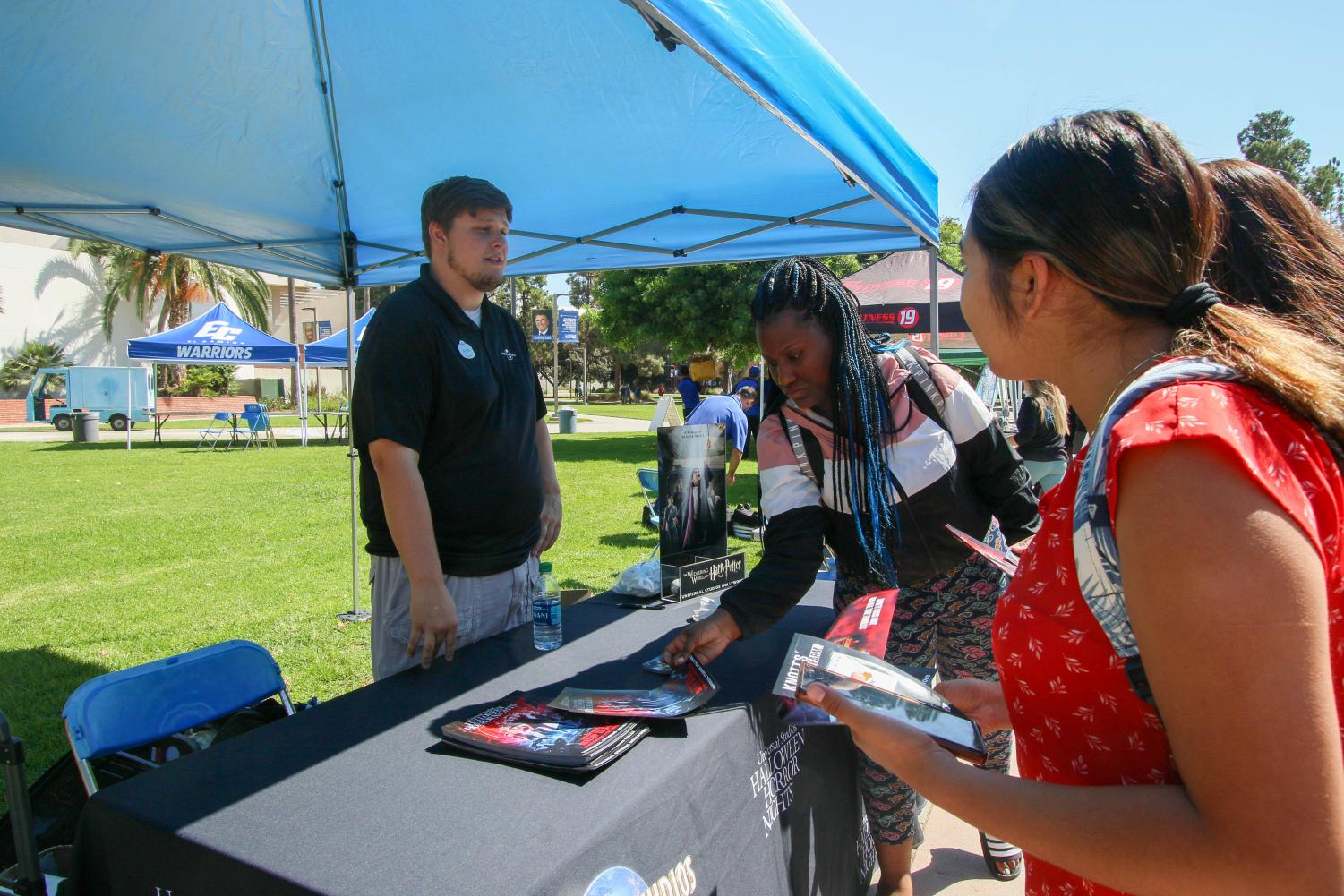Universal Studios Corporate Sales Representative Austin Jacobs, 23, explains discounts that are offered to El Camino College students during the ASO Discount Fair at the Library Lawn on Wednesday, Oct. 4.