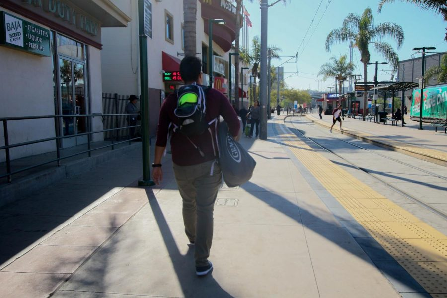 Emilio Pensado walks the streets of San Ysidro with bags of women
