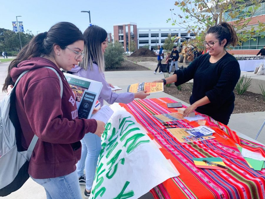 Kimberly Garcia, who works at the First Year Experience office, hands out flyers for Undocumented Students Week of Action at the Hispanic Heritage Month Kickoff Festival on Tuesday, Oct. 1. The week will advocate and provide resources for undocumented students like workshops and other activities. Rosemary Montalvo/The Union