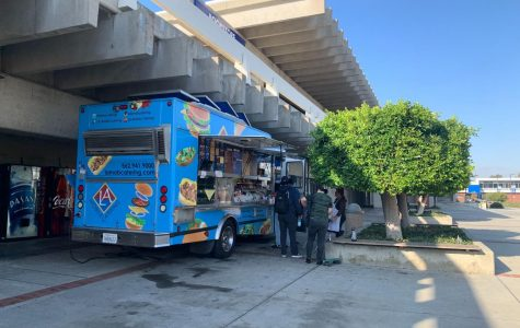 Students order food from the LA Mobile Catering food truck located next to the El Camino College Bookstore on Tuesday, Oct. 8. The truck was brought on El Camino College to rectify food options available to students on the north side of campus two years after The Manhattan Deli closed down. Rosemary Montalvo/The Union