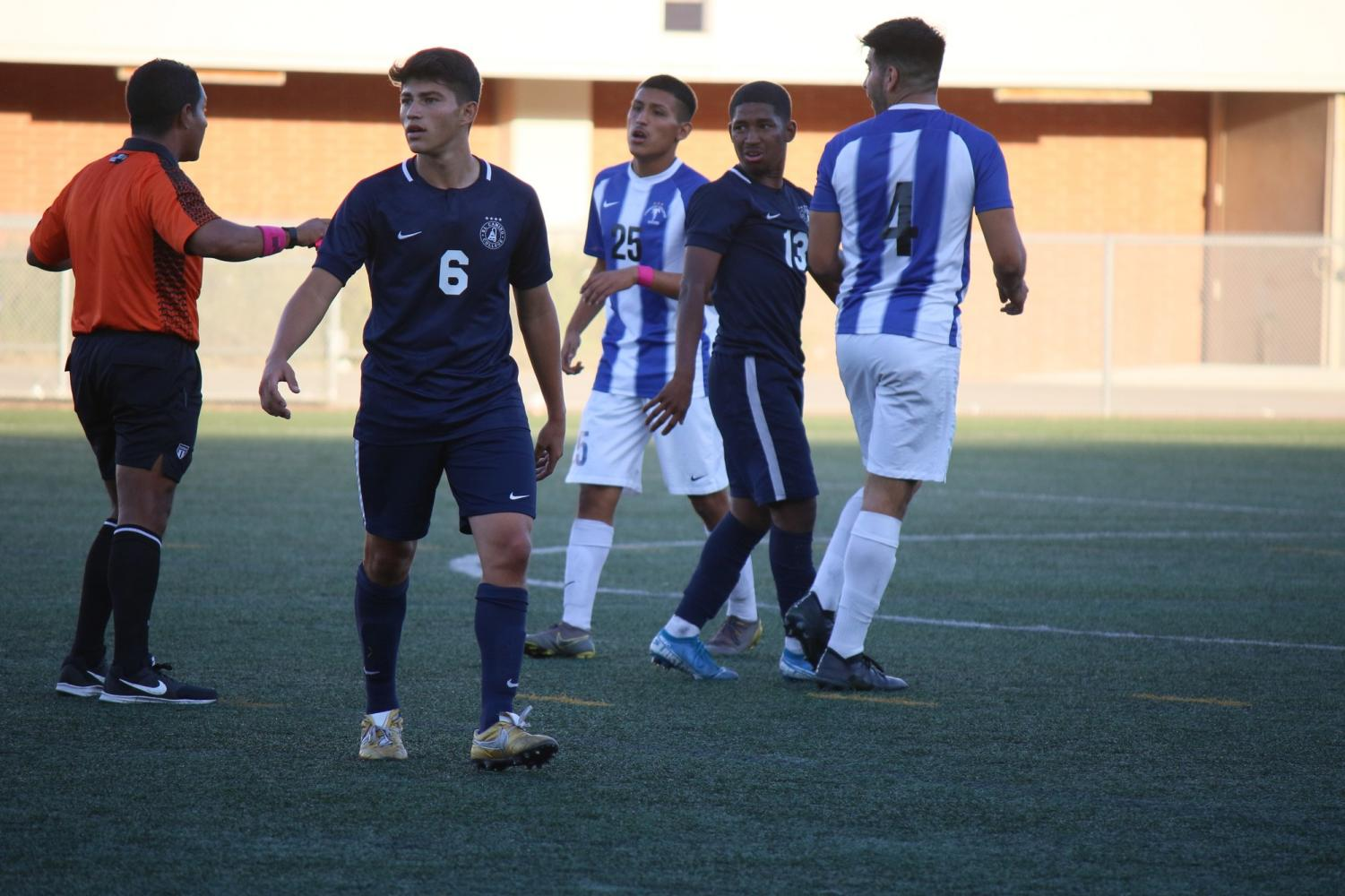 The referee talks to Cerritos and El Camino College's men's soccer team players after tensions flared during the game at the PE and Athletics Field on Friday, Oct.11. There were a total of 32 fouls recorded in the match. Viridiana Flores/ The Union