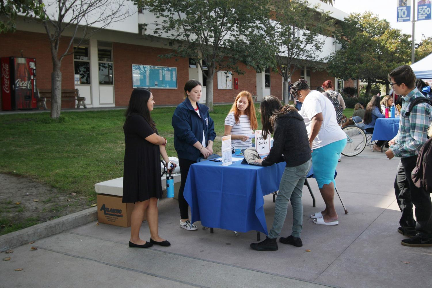Students line up and sign in to the Harvest Festival near the Student Services Building on Tuesday, Nov.19. They received a paper to fill up with stickers available at the booths they visited during the event. Viridiana Flores/The Union