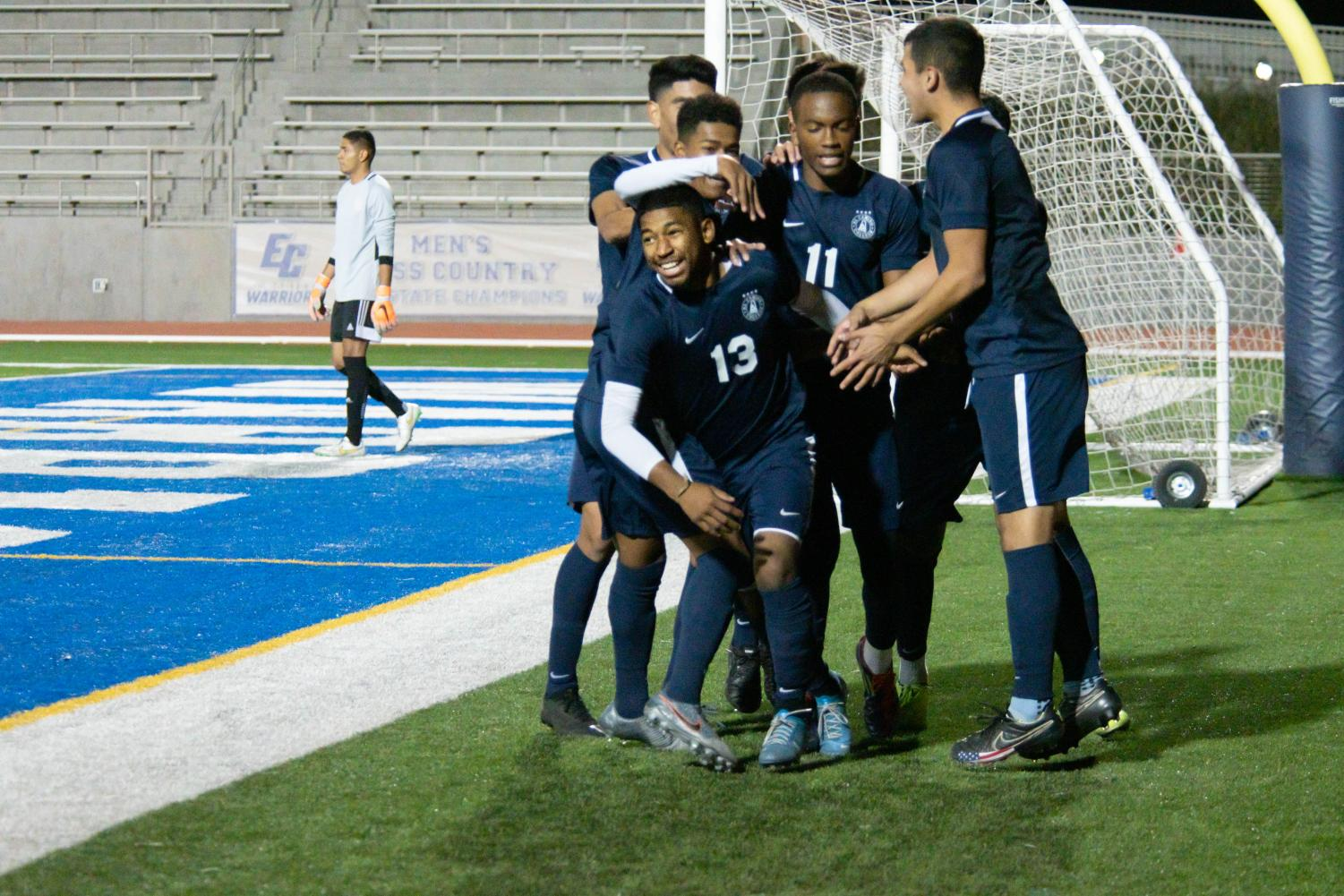 """Players from the El Camino College men's soccer  team surround and cheer on Melvyn Perez-Cortez, No. 13, after he scored a goal against Orange Coast College in the 48th minute of the match at Murdock Stadium on Tuesday, Nov. 26. """"At halftime we had a speech with the coach and he said to 'come out strong' and that's what we did and it benefited us a lot and [the game] went in our favor,"""" Perez-Cortez said. Rosemary Montalvo/The Union"""
