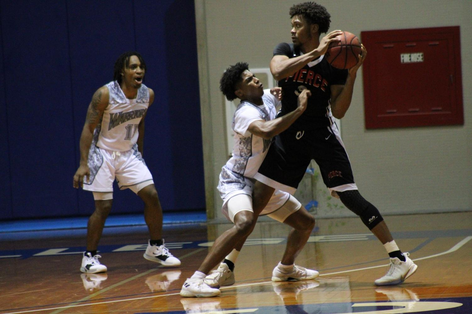 El Camino College men's basketball guard Corey Madison plays tight defense on Los Angeles Pierce College Dallas Johnsons while fellow Warrior Oshuia Alston encourages him and awaits on the side during the game Wednesday, Nov. 6, at ECC's North Gym. Jaime Solis/The Union