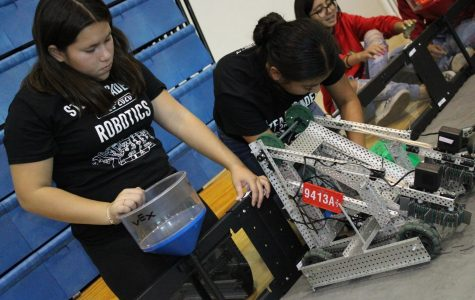 Members from Team Las Reinas make adjustments to their robot at the practice fields during the VEX Robotics Competition hosted by the El Camino Robotics Club in the South Gymnasium on Saturday, Nov. 9. The competition is a fundraising event for the El Camino Robotics Club that brings kids together to create machines that complete objectives. Jaime Solis/The Union