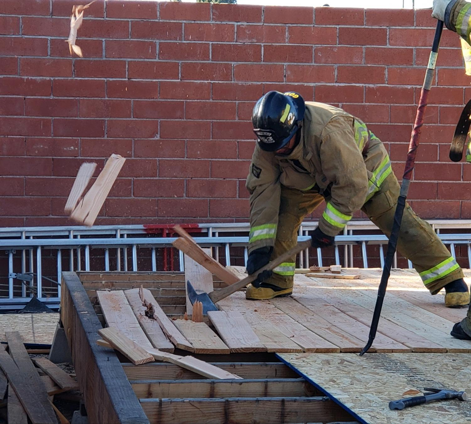 El Camino College Fire Academy student Alex Gomez practices cutting holes in wooden boards with an axe for roof operations Wednesday, Oct. 23. The academy, formerly known as the South Bay Fire Academy, has been training firefighters for 50 years. David Rondthaler/The Union
