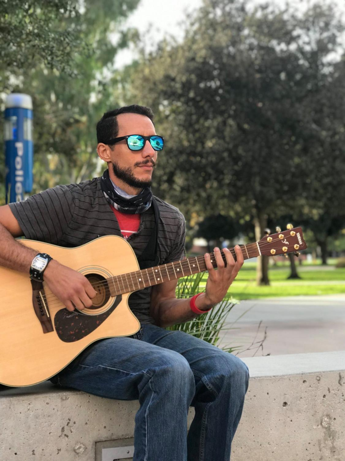 """Michael Nicoli Ferrey, 32, music major, plays his guitar at his regular spot between the MBA and Music Buildings at ECC on Oct. 14. Nicoli is a multi-musician who also plays the piano, drums and bass. """"Currently my goals consist of recording my music successfully finally because it's been a long process that I haven't accomplished yet,"""" Nicoli said."""