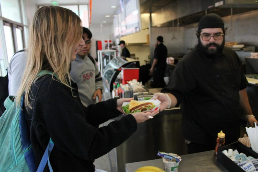 Annika Waisanen, health and exercise science major, receives her order from a worker in Cafe Camino on Tuesday, Dec. 3. The facility was given a 91% on its recent health inspection by the Los Angeles County Department of Public Health on Thursday, Sept. 5, according to its results. Jaime Solis/The Union
