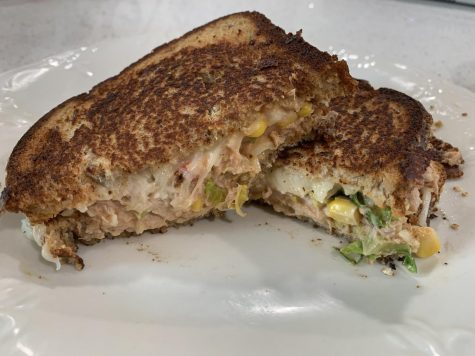 Spicy tuna melt sandwich posed on a white plate.