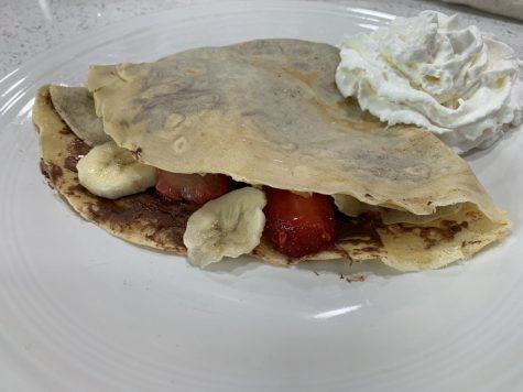 Strawberry, banana, and chocolate crepe plated with whipped cream. Oscar Macias/ The Union.