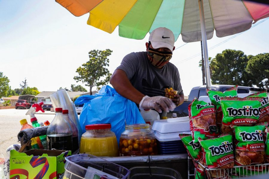 ")Luis, an eletoro/street corn vendor, fills a cup with fruit as he continues to make his weekend route through a neighborhood in Riverside during the stay- at-home order. ""It's actually going very well. Since more people are home, I sell more,"" Luis said. (Rosemary Montalvo / Warrior Life"