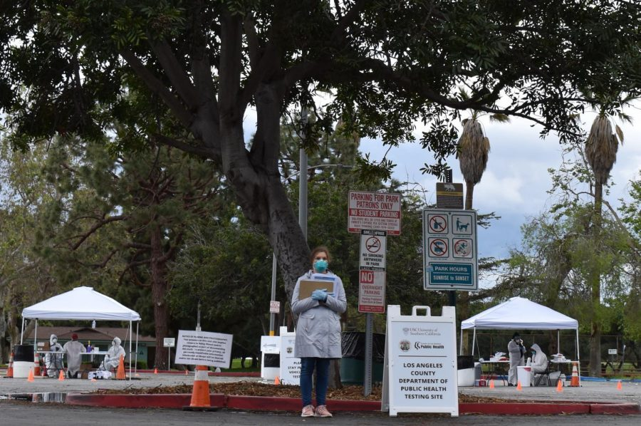 A healthcare worker stands at a drive- thru COVID-19 testing site at Alondra Park in Lawndale, on Friday, April 10. The county of Los Angeles has set up 25 drive-thru test-sites in an effort to track and contain the virus. (Heather Guzman / Warrior Life)