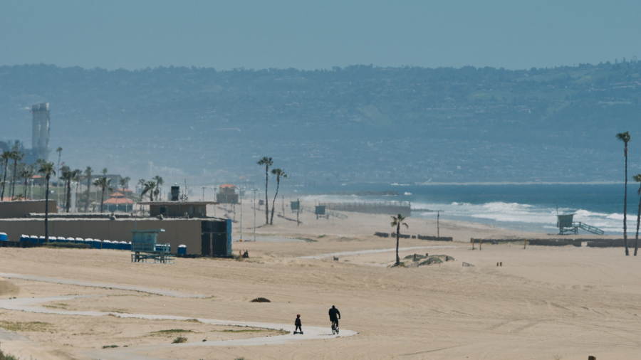 A man on a bicycle and a child on a Hoverboard cruise by the So Cal Gas Tank Farm in Playa Del Rey, on Sunday, April 12. Governor Gavin Newsom ordered California beaches to be closed on May 1 in an effort to lessen the spread of COVID-19. (Cameron Klassen / Warrior Life)