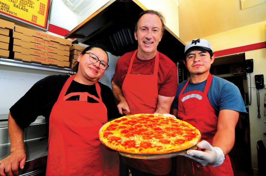 Bob Gilewski [middle], flanked by workers Lidia Ortega [left] and Josue Aquino, poses with a large pepperoni pizza from the oven. The New York style pepperoni pizza is one of many classics on GiGi's menu and is freshly prepared each day. Photo credit: Rachel Maldonado