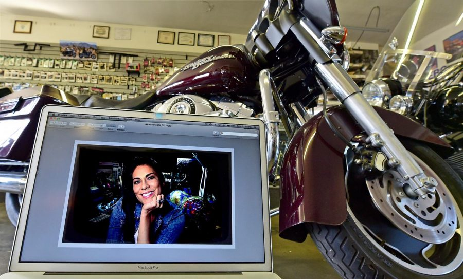 "Practicing safe distancing, EC student Michele Matamoros is seen here in a self-portrait taken at her Koreatown apartment. Her ""selfie"" was then displayed on a laptop screen and rephotographed at Motorcycle Michael's Gardena bike shop Photo credit: Gary Kohatsu"