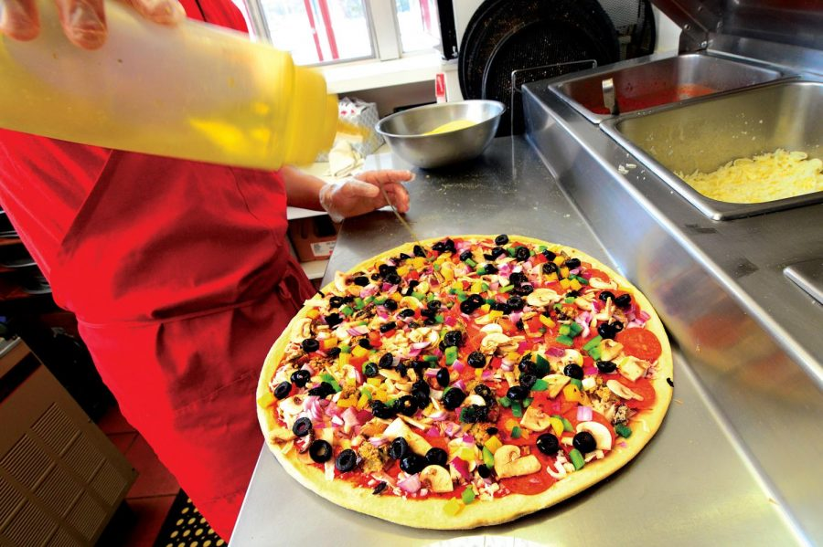 A Gigi's worker applies the finishing touches to a pizza, just before baking. The eatery near El Camino College is known for its New York-style pizza.