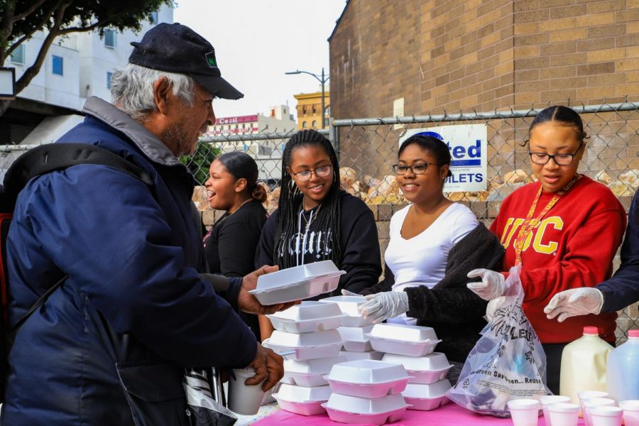 Friends and volunteers of the Helpful Homegirls distribute plates of food and beverages to the homeless in Downtown L.A. on Saturday, Dec. 21.
