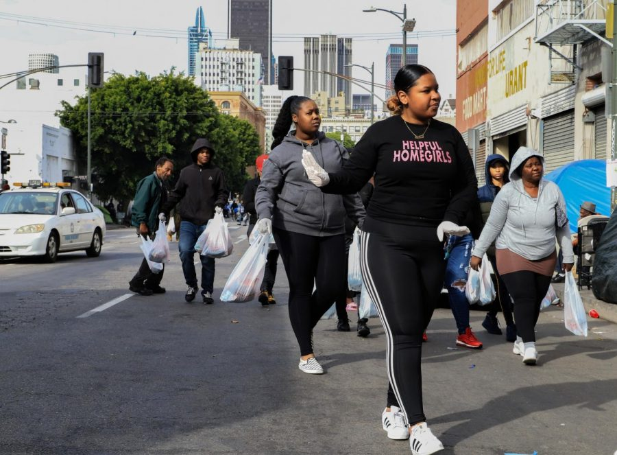 China leads the group of volunteers–each carrying care packages for the homeless–down a street in Downtown L.A., Sat. Dec. 21.