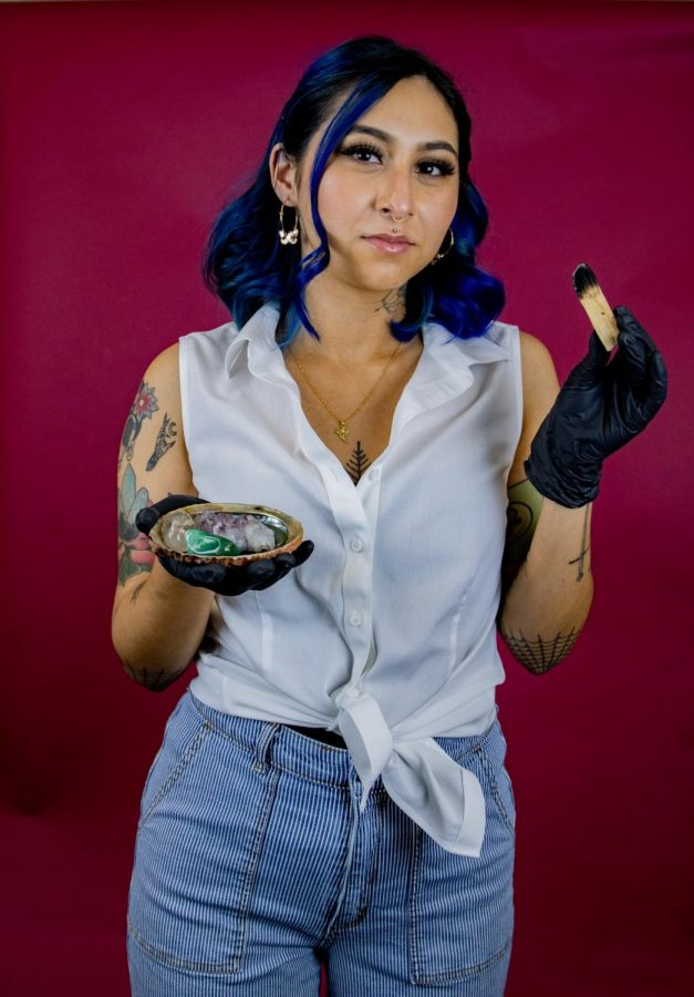 Nina Rojas holds a piece of Palo Santo wood in her left hand, that she uses for spiritual cleansing. In the other hand are the crystals jade, clear quartz and purple amethyst.
