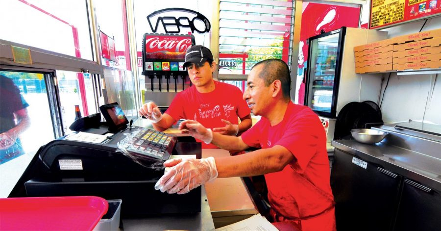 Gigi's workers Josue Aquino, [left], and Sylvester Gutierrez man the registers as well as prepare the pizzas and other menu items. Both are longtime employees of the establishment.
