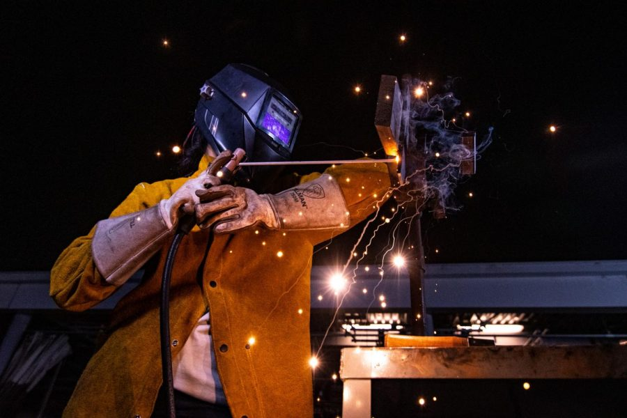 "Sparks fly as 24-year-old welding student, Samantha Schreider molds two metal pieces together using a technique called shielded metal arc welding. This form of welding compared to variations like tungsten arc welding is the ""messiest"" because it results in a surplus of embers that requires adequate protection–like the yellow cow-hide jacket Samantha wears. Photo credit: Rosemary Montalvo"
