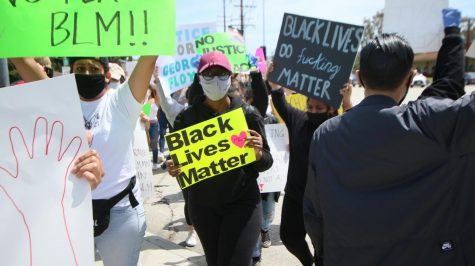 "A protester holds up a ""Black Lives Matter"" poster as she strides through a crosswalk on Madrona Avenue. On Sunday, May 31, there were a series of protests in response to the death of George Floyd. This demonstration occurred at Torrance Boulevard and Madrona Avenue at 1 p.m., near Torrance City Hall. Molly Cochran/The Union"