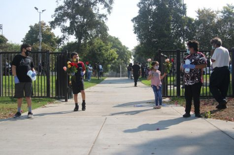 (from left) Jordan Melendez, Nathan Melendez, Katelyn Melendez, and Marco Leon, stand outside the park distributing flowers and masks to attendees for the vigil held for Juan Carlos Hernández on Sunday, Oct. 4, in Martin Luther King Jr. Park.
