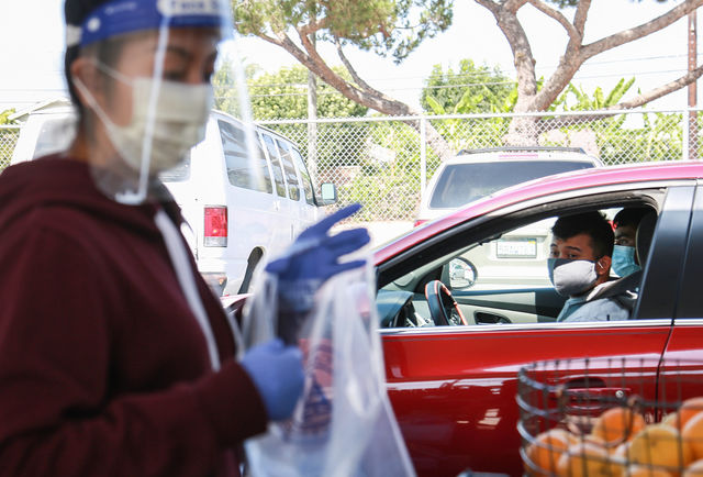Yorgely Vital-Jimenez, a volunteer at the Warrior Pantry, gathers oranges for a student who stopped by in their car to pick up food in El Camino College's Parking Lot B on Tuesday, Sept 22. A variety of products can be picked up by EC students who need help accessing essentials such as food and cleaning supplies. (Mari Inagaki/ The Union)