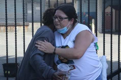 Yajaira Hernández, Juan Carlo's mother, recieves a comforting hug from Kathy Stewart, 44, one of the nearby Downtown Los Angeles residents who partook in the food distirbution in honor of Juan Carlos on Thursday, Oct 15. Several of those who recieved supplies from the Hernández family stopped to chat and offer condolences and support to the suffering family members. (Jaime Solis/ The Union)
