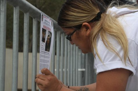 Stephanie Mendoza puts up a missing persons flyer on the barricade around the Downtown Los Angeles Police Department during a protest held for Juan Carlos Hernández on Sunday, Oct. 25. Several of these posters were put up around the Police Department, on flag poles, barricades and walls, but have all be subsequently torn down. (Jaime Solis/ The Union)