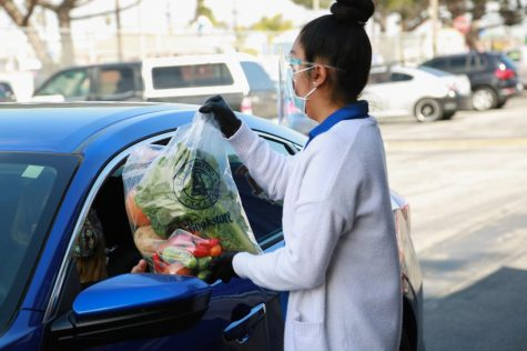 Yorgely Vital-Jimenez, a volunteer at the Warrior Pantry, give fresh vegetable for student in Warriors Drive Thru Pick Up Event at El Camino parking lot B, March 17, 2021.