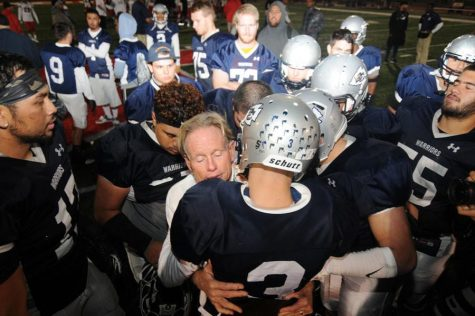 Coach John Featherstone gives quarterback Jorge Hernandez a hug after the game versus Long Beach City College on Nov. 14, 2015.