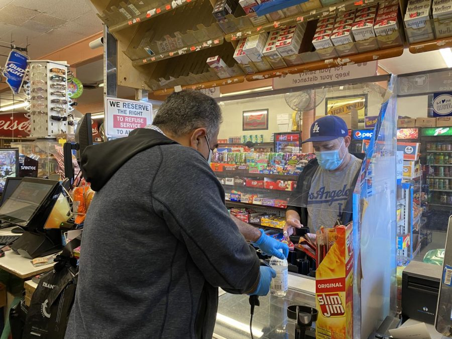 Owner, Alex Gonzalez, helps a local resident check out an item on Feb. 24, 2021 in Torrance, Calif. Many residents are regulars at the liquor store and come in everyday to buy items needed at home. (Abigail Puentes/ The Union)