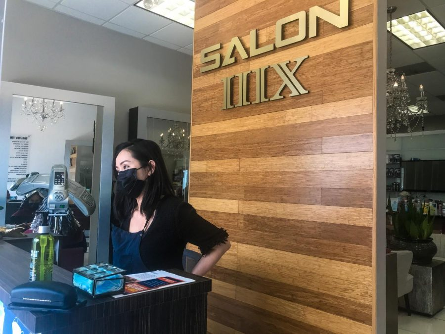 Lily Ngo, owner of Salon 310-IIIX, eagerly awaits customers at the front kiosk of her salon in Carson while wearing a mask and a styling apron on Sunday, March 14. She is one of many female business owners impacted by the COVID-19 pandemic that have stayed determined to keep their businesses afloat. (Maureen Linzaga/ The Union)