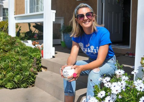 """Erica Brenes, associate English professor at El Camino College, sits next to a bed of freshly bloomed daisies on her front porch in Long Beach on March 24. Brenes feels that poetry is a great vehicle to help her students connect with the humanities. """"Poetry asks you to have a heightened awareness about the way you choose to spread and share your message,"""" Brenes said. (Walter Jay Jr. / The Union)"""