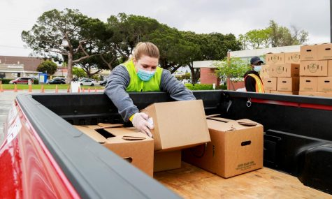 Laura Goodman loads box of food onto an attendee's car during the Wondalunch event on Saturday April 24, at El Camino College's parking lot B. Stacks of boxes filled with food were prepared for distribution for this event. (Mari Inagaki/ The Union)