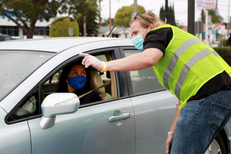 David Mcdonald, one of the workers at the Wondalunch event, directs an attendee of the Wondalunch event, Saturday April 24,at El Camino College parking lot. Masks were required to attend and social distancing measures were observed during the event. (Mari Inagaki/ The Union)