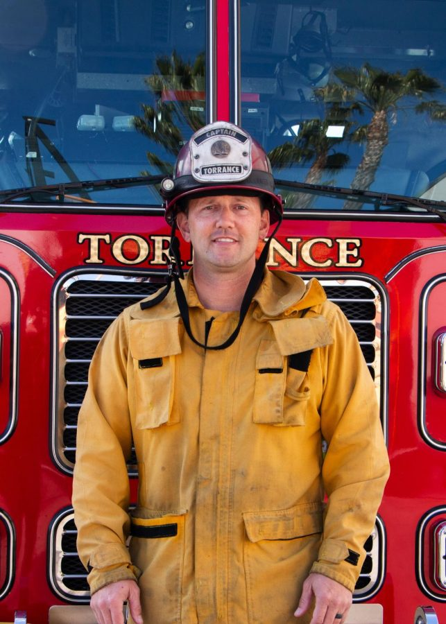 Adam Brown poses in front of a Torrance fire engine. He is a captain for the Torrance fire department, a part time recruit trainer for Torrance Fire department and a part time instructor at El Camino College. Adam shares his 25 years of knowledge and dedication with his trainees and students, and hopes to help prepare them for the obstacles that they will face in the firefighting industry. Photo taken on Wednesday, March 31. (Patricia Carrillo/ Warrior Life)