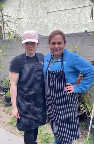 "Lourdes Vazquez Mejia (left) and her mother, Sandra Vazquez (right) pose for a photo between prepping meals for customers at Birreria3rageneracion, the restaurant they run out of their home backyard in Harbor City, on May 2. Photo credit: Jesus ""Jesse"" Canche Chan"