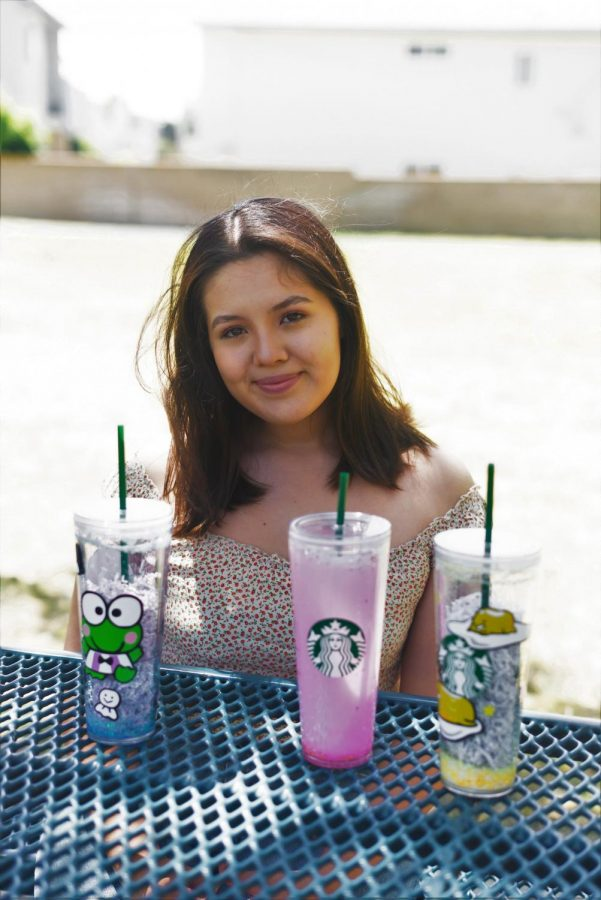 Michelle Mondragon poses, smiling, next to some of her most recent orders that have been finished. Each cup order goes for about fifty dollars. Image taken on May 2. (Francisco De La Cruz/ The Union)